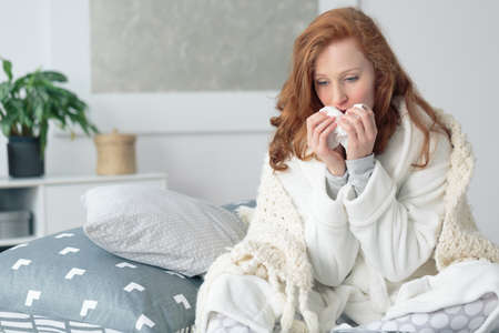 Foto de Miserable woman sitting on the bed wrapped in blanket, feeling sick with flu, having fever and blowing runny nose with handkerchief - Imagen libre de derechos