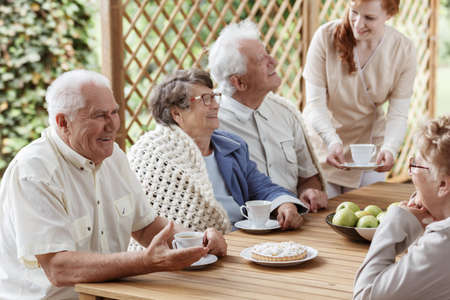 Foto de Seniors sitting by the wooden table with pie and white coffee cups - Imagen libre de derechos