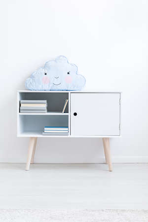 Foto de close up of blue cloud pillow on cupboard in white kid's room - Imagen libre de derechos