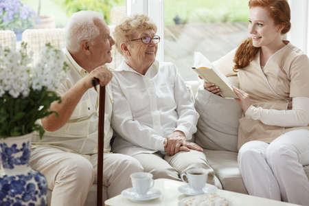 Foto de Elder married couple sitting on the couch and smiling at nurse with a book - Imagen libre de derechos