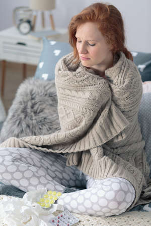 Foto de Young ill woman wrapped in a warm blanket feeling cold sitting at home with pills for sore throat and tissues - Imagen libre de derechos