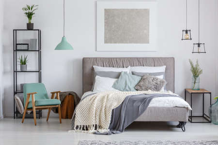 Foto für Silver painting above king-size bed with knit beige blanket in adorable bedroom with mint retro chair - Lizenzfreies Bild