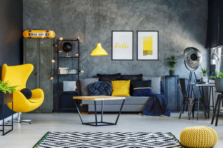 Photo pour Yellow lamp above table in living room with grey sofa, yellow pouf and designer chair - image libre de droit
