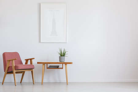Photo pour Simple painting above wooden table with plant in grey pot next to powder pink vintage chair - image libre de droit