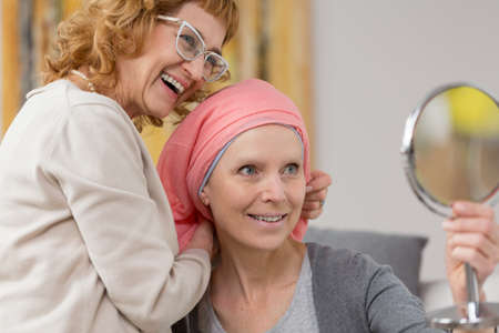 Foto de Woman after chemotherapy receiving a new, red scarf from a friend, and trying it on while looking into the small mirror - Imagen libre de derechos