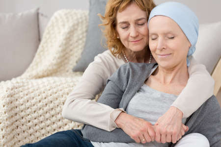 Foto de Woman with a necklace comforting her friend with cancer, both of them have their eyes closed - Imagen libre de derechos