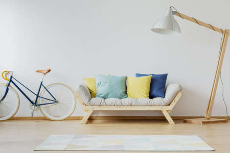 Foto de Colorful pillows on couch in modern scandinavian flat with wooden couch, lamp, rug, vintage bike and white wall - Imagen libre de derechos