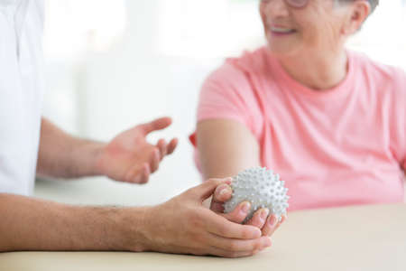 Foto de Nursing home patient doing active pnf exercises with a grey spiked ball used for rehabilitation purposes - Imagen libre de derechos