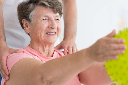 Foto de Elderly woman enjoying her isometric exercises with a yellow, spiked massage ball - Imagen libre de derechos