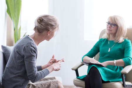 Foto de Female patient talking about her worries with therapist in the office, psychotherapy and mental health concept - Imagen libre de derechos