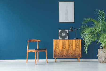 Photo pour Stylish apartment interior with blue wall decorated in vintage style with wooden cupboard,chair, mock-up poster and tropical potted plant - image libre de droit
