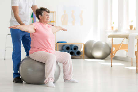 Foto de Elderly senior ward trying to maintain balance while sitting on a grey fit ball while being supported by physiotherapist - Imagen libre de derechos