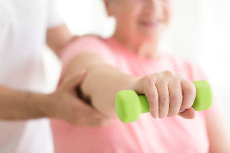 Foto de Elderly patient holding a minor dumb-bell in her right hand during isometric physiotherapy - Imagen libre de derechos