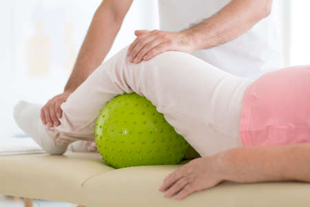 Foto de Senior patient undergoing rehabilitation in a hospital with a green massage ball under her left leg - Imagen libre de derechos