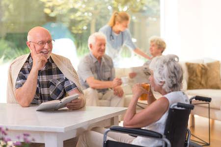 Photo pour Elder man with a book talking to disabled woman drinking tea - image libre de droit