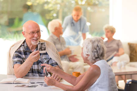 Photo pour Husband in glasses sitting by the table and showing old photos to his wife with Alzheimer's disease at the rest home - image libre de droit