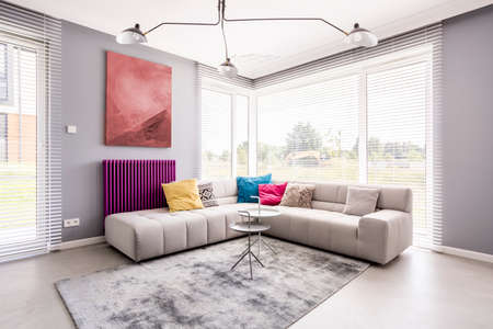 Photo pour Two small tables standing on a soft, grey carpet by the sofa in the corner of a living room and an abstract painting on the wall - image libre de droit