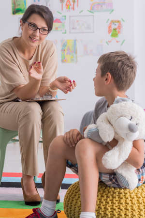 Foto de Boy is holding stuffed toy and is looking at pedagogue during therapeutic meeting in classroom - Imagen libre de derechos