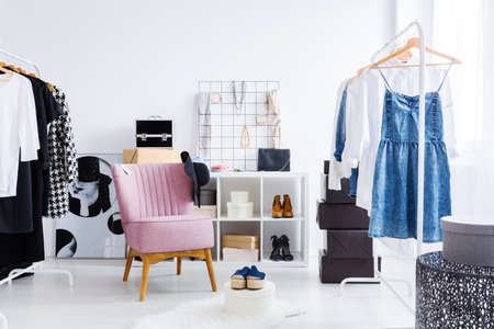 Photo pour Pink chair in bright dressing-room with clothes shoes and jewelry on shelf. Fashionable dressing room concept - image libre de droit