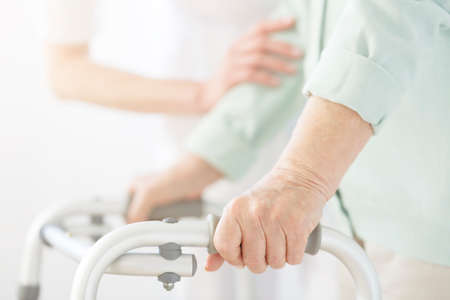Foto de Nurse in white uniform supporting elderly person using a walker at nursing home - Imagen libre de derechos
