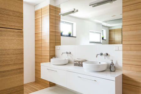 Foto de Elegant bathroom with two sinks, mirror and wooden design - Imagen libre de derechos