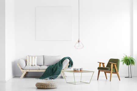 Foto de Dark green blanket thrown on grey sofa in bright living room with empty poster and armchair - Imagen libre de derechos