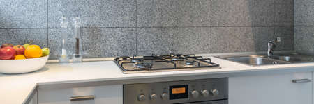 Photo for Part of the kitchen with a white table top, silver stove and sink - Royalty Free Image