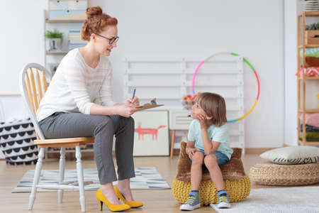 Foto de Friendly young child psychologist talking with little boy suffering from emotional disorder in bright office - Imagen libre de derechos