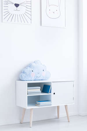 Foto de Posters above cupboard with blue creative pillow and books in child's room - Imagen libre de derechos