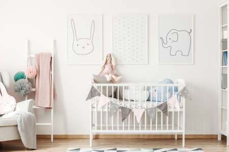 Foto de Child size bed standing under cute animal posters hanging on white wall and a small ladder - Imagen libre de derechos