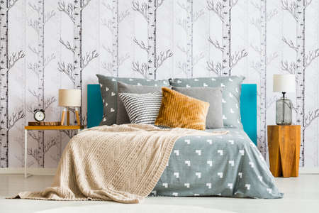 Foto de Close-up of cozy bed with gray bedsheets and beige blanket against white wallpaper with forest motif - Imagen libre de derechos