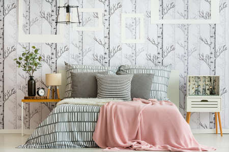 Photo pour Feminine bedroom interior with forest inspired decorations and geometric bedding - image libre de droit