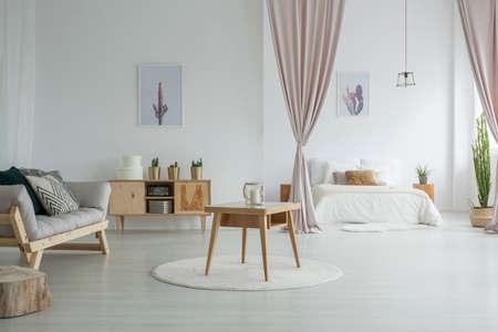 Foto de Spacious living room with wooden table on white carpet, rustic cupboard and grey sofa near open bedroom - Imagen libre de derechos