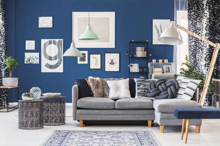 Photo pour Designer metal tables near grey corner couch in spacious living room with gallery on blue wall - image libre de droit