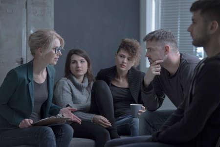 Foto de Support group meeting with female psychologist in a dark room - Imagen libre de derechos