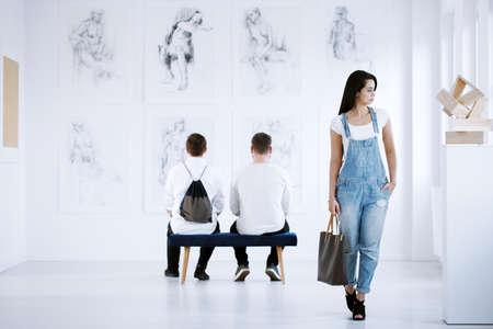 Foto de Art gallery exhibition presenting stylish paintings showing women acts - Imagen libre de derechos