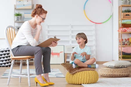 Foto de Cheerful young kid talking with helpful child counselor during psychotherapy session in mental health center for children - Imagen libre de derechos