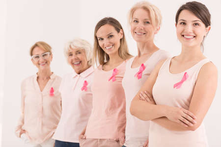Foto de Women of five generations standing in a row wearing pink ribbons as the symbol of breast cancer struggle - Imagen libre de derechos