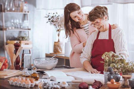 Foto de Smiling woman massaging grandmother's shoulder while making cake in the kitchen - Imagen libre de derechos