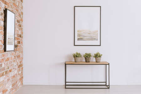 Foto de Three potted plants standing on a wooden console table against white wall with simple painting in neutral colors - Imagen libre de derechos