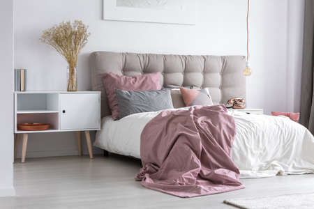 Photo pour Gray tufted headboard and pink bedcover in simple bedroom with minimalist interior design and copper accessories - image libre de droit