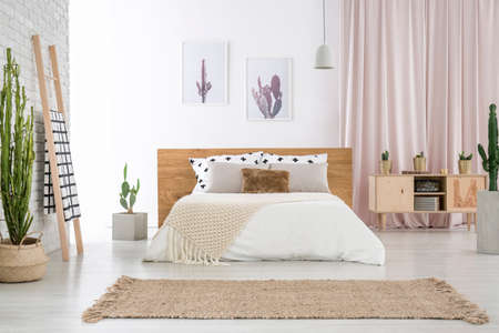 Photo pour Beige carpet in front of king-size bed near ladder and cupboard in spacious bedroom with cactus motif - image libre de droit