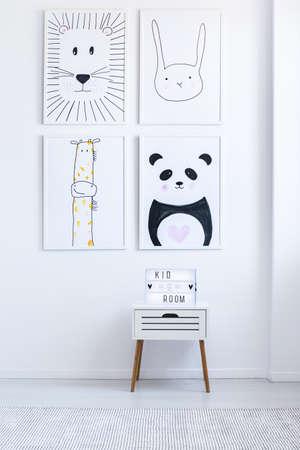 Foto de Black and white drawings on wall above cabinet in white autistic kid's room - Imagen libre de derechos