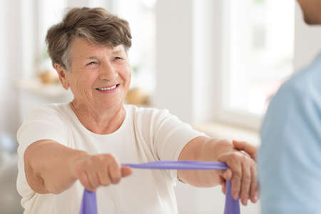 Photo for Smiling senior woman doing strength exercise with elastic band during fitness class - Royalty Free Image