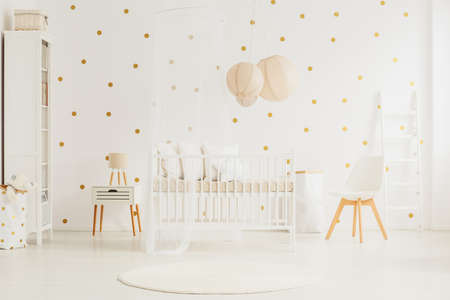 Photo pour Wooden crib with canopy and pillows in white baby room with dotted wall and lanterns - image libre de droit
