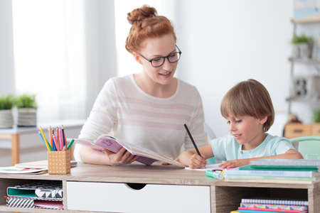 Photo for Female private tutor helping young student with homework at desk in bright child's room - Royalty Free Image