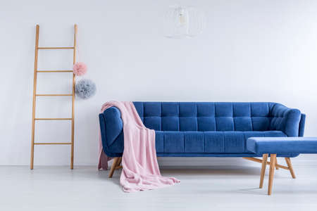 Foto de Pink coverlet thrown on the blue comfy couch in room with wooden ladder and empty white wall - Imagen libre de derechos
