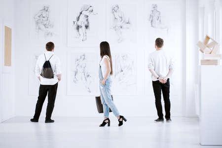 Foto de Art gallery visitors marveling at paintings that reveal women nudity - Imagen libre de derechos