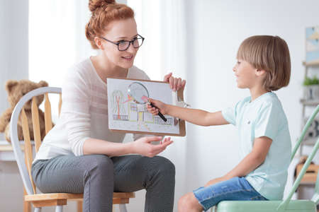 Foto de Child adoption and family concept, psychotherapist working with young boy discussing together a house of his dreams in foster care - Imagen libre de derechos