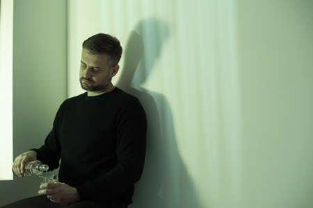 Foto de Adult man with bad habits pouring vodka into glass while sitting alone at home - Imagen libre de derechos